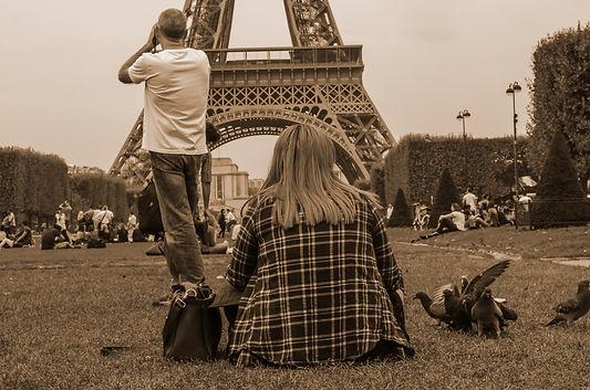 Fotografia fine art em sépia de jovem sentade e homem de pé abaixo da Torre de Paris, ambos de costas, ele com camiseta branca e jeans, ela com camisa quadriculada.