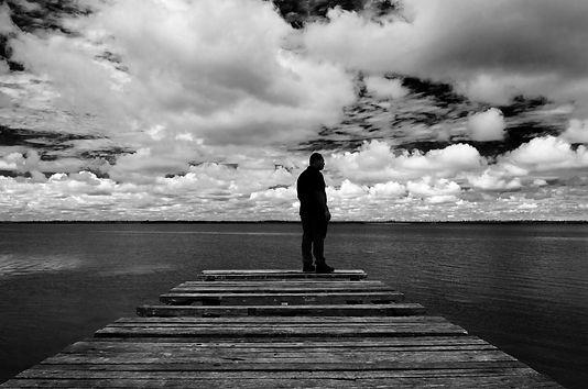 Fotografia fine art de silhueta de homem de pé em tablado com nuvens ao fundo em preto e branco. Photograph fine art of silhouette of man standing on sidewalk with clouds in the background in black and white.