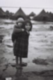Egy kislány fiatalabb testvérét viszi a hátán egy téli napon Beit Lid bevándorlótáborban, 1950. január 1.