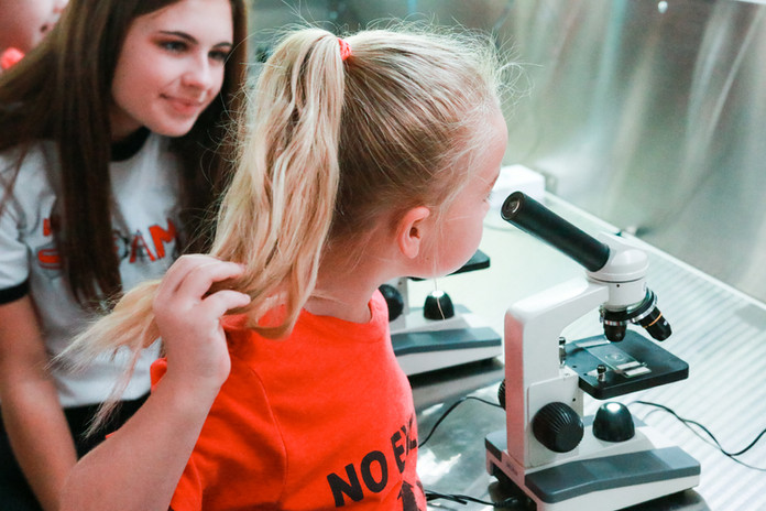 iTeam member with student on microscope.