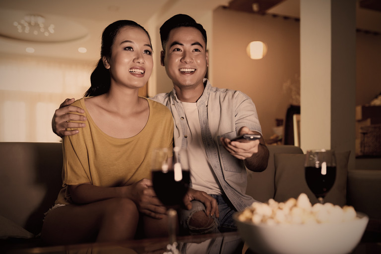 Smiling-couple-watching-tv-on-sofa-51320