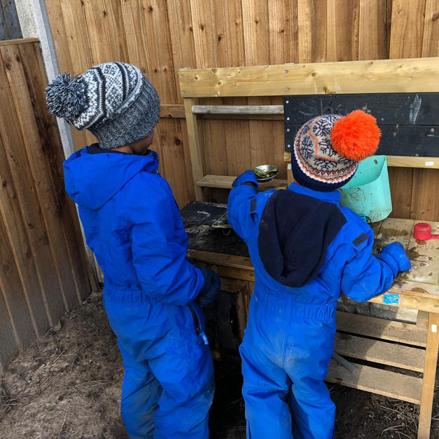 Ace and Shay in the mud kitchen