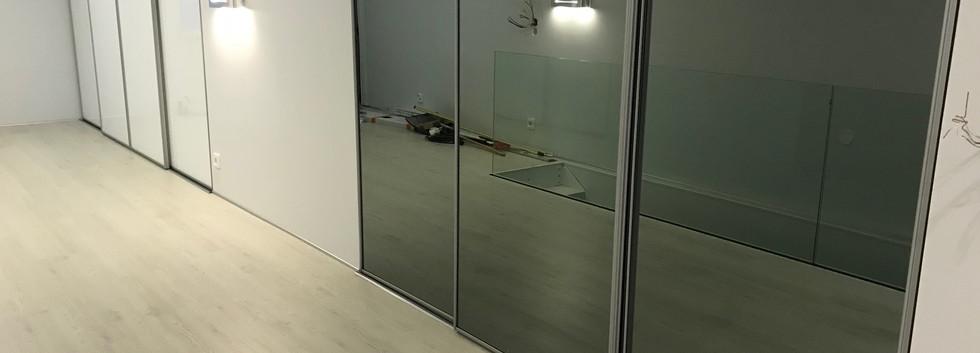 Harmaa teräskehä ja valkoinen lasi sekä harmaa peili