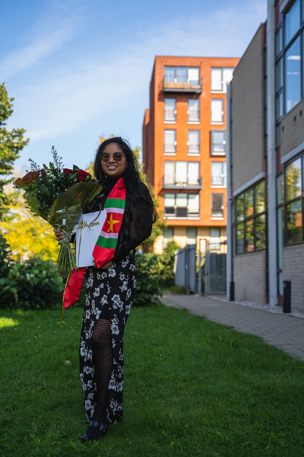 Fariel Soeleiman posing with her HKU diploma, holding a bouquet of roses.