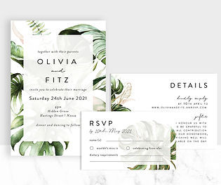 Lush tropical greenery and floral wedding invitation suite