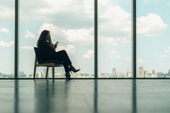 woman-sitting-on-phone-in-modern-office-