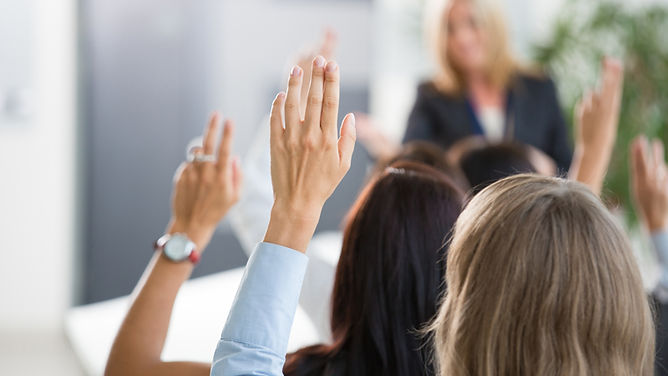 people raising their hands at a meeting