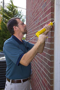 Contractor caulking exterior walls betwe