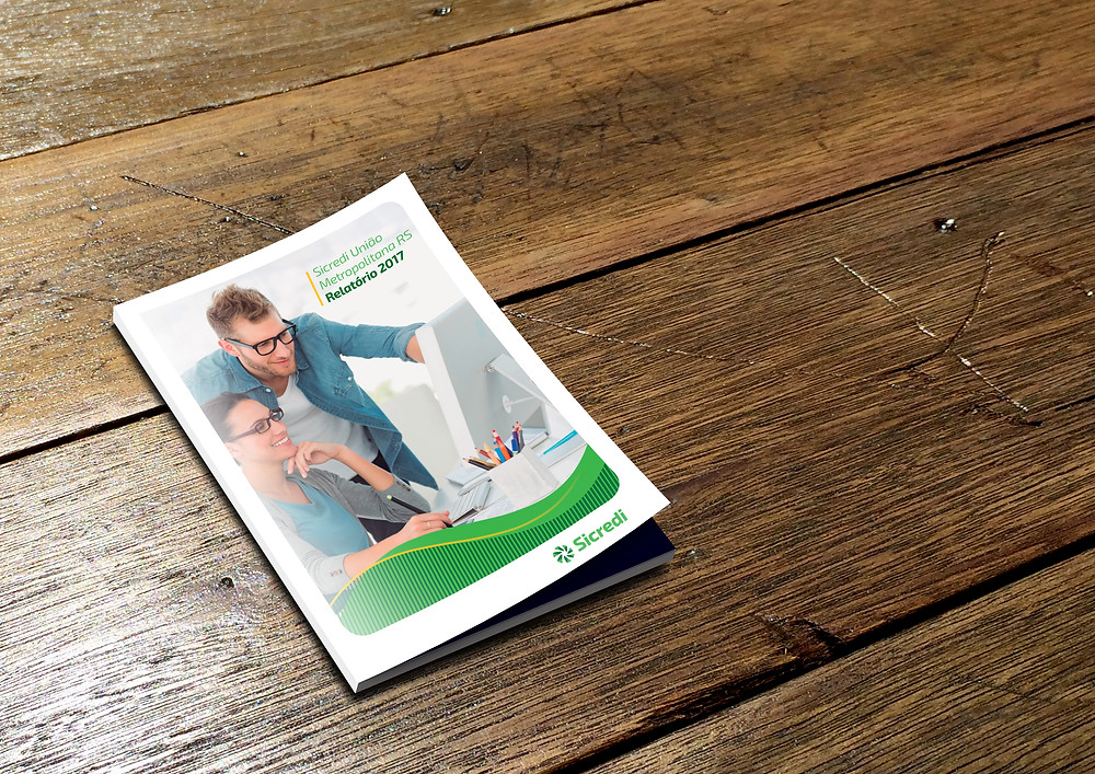 Reprodução da capa do Relatório Anual de 2017 da Sicredi Metropolitana RS. A publicação está sobre uma mesa de madeira. Na capa, o título está alinhado à direita, na parte superior. Na parte inferior, o logotipo da instituição. A imagem apresenta um homem e uma mulher conversando e trabalhando em frente a uma mesma tela de computador.