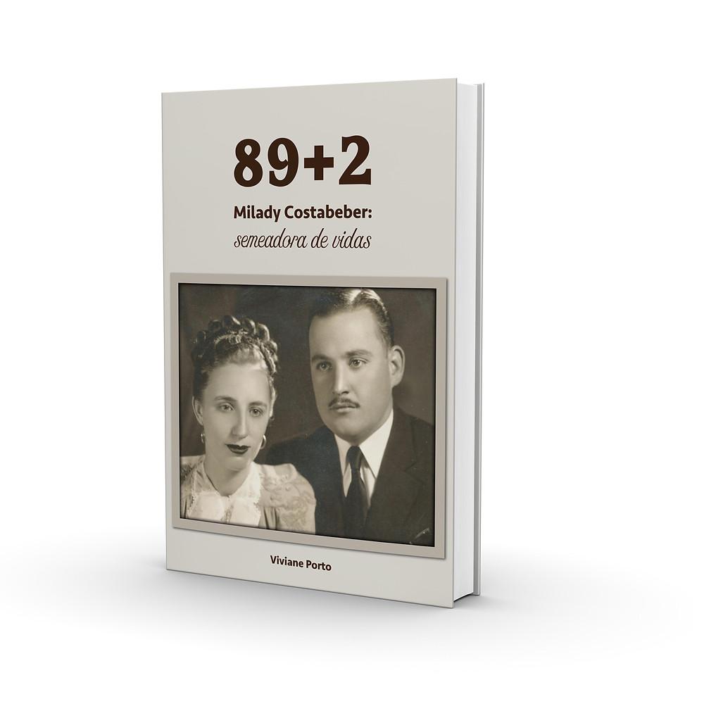 """Reprodução de capa do livro """"89+2 Milady Costabeber: semeadora de vidas"""". O título está centralizado, na parte superior da capa. Ao centro, uma foto da personagem principal com o marido, em preto e branco. Na parte de baixo do livro, centralizado, está o nome da autora, Viviane Porto."""
