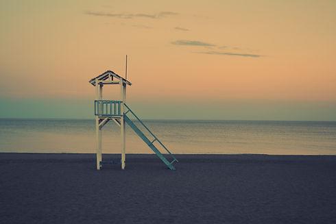 lifeguard tower on beach at sunset