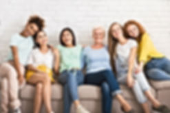 diverse-women-hugging-sitting-on-couch-a