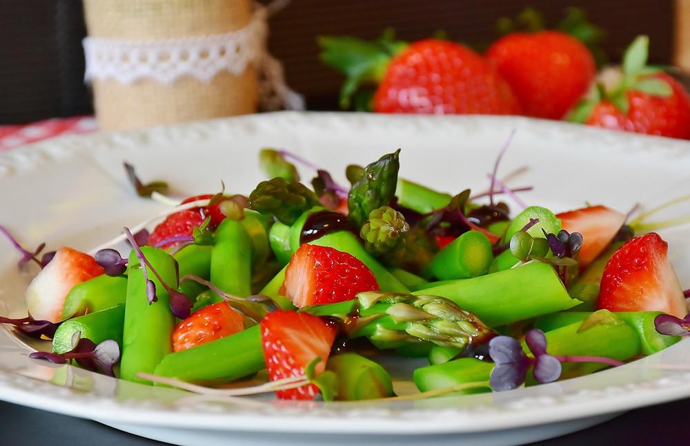 Grüner Spargel mit frischen Erdbeeren und saftigen Wiesenblümchen garniert
