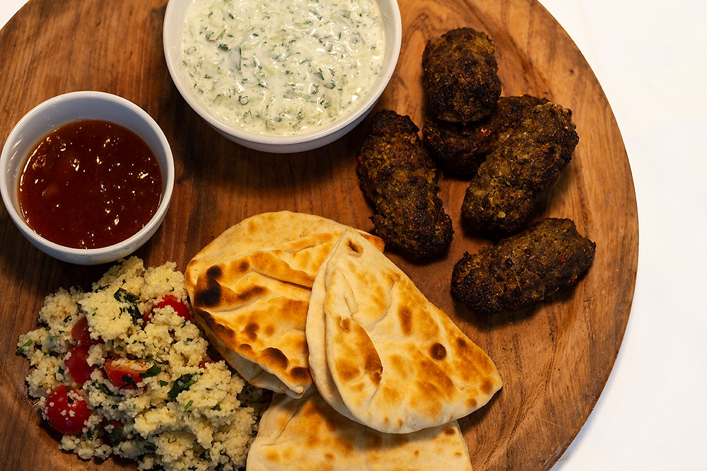 An image of spiced beef koftas on wooden chopping board.