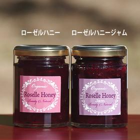 (左)ローゼルハニー 無農薬・自家栽培のハイビスカスローゼルを永田養蜂の八百津産蜂蜜に漬け込みました。きれいなルビー色のハーブハニーです。爽やかな酸味があり、パンだけでなく、アイスクリームやヨーグルトと合わせて食べるのもおすすめです。 ● 内容量:135g ¥900 型番:RH   (右)ローゼルハニージャム 無農薬・自家栽培のハイビスカスローゼルを蜂蜜で煮てジャムに加工しました。きれいなルビー色のハーブハニージャムです。爽やかな酸味があり、パンだけでなく、アイスクリームやヨーグルトと合わせて食べるのもおすすめです。 ● 内容量:135g ¥950 型番:RHJ