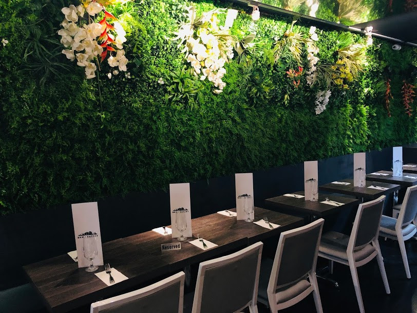 BKK Eatery flower wall with more dining tables with chairs