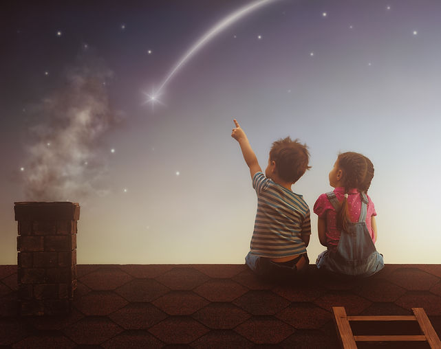 ילד וילדה יושבים על גג בית ומצביעים על כוכב נופל