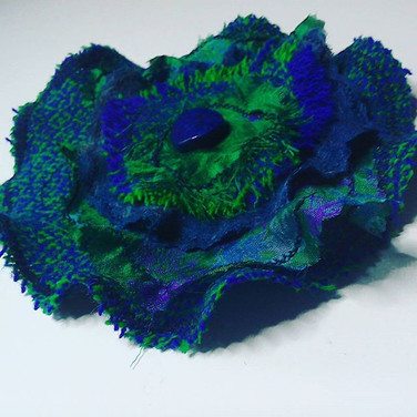 Harris Tweed and silk corsage in purple and green. Available from Handmade at the Scottish Wool Centre, Aberfoyle.