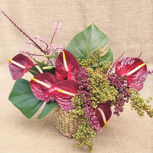 Arranjo com anturios, vegetação e sementes no cesto de palha