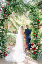 Bride and Groom Under Floral Decorated Arbor at Blackstone Rivers Ranch