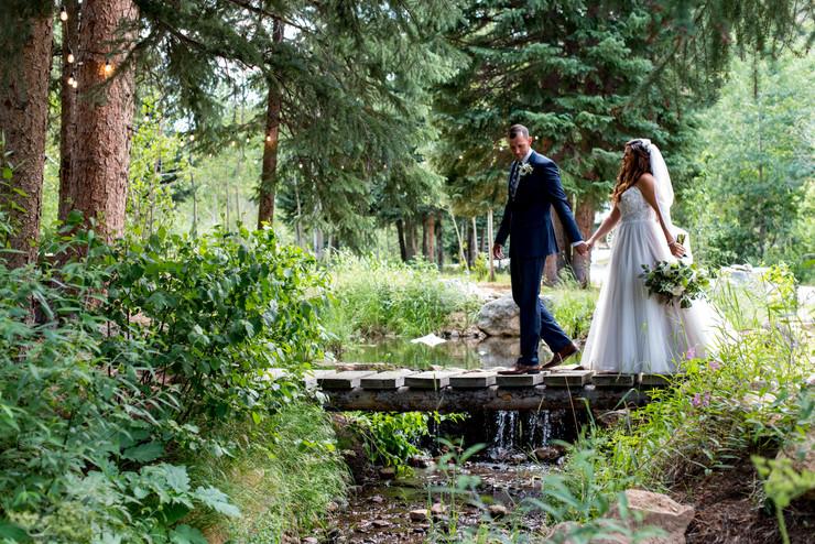 Bride and groom stroll over bridge