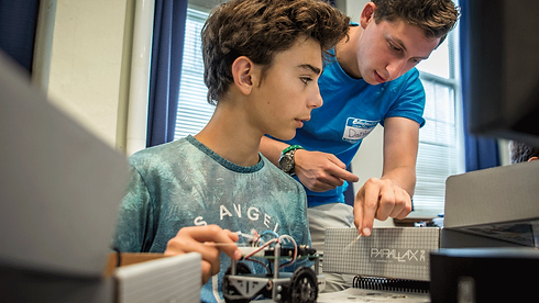 An Emagination Tech Camper being taught about Robotics