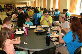 A group of campers and counselors eating lunch together