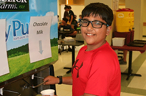 A tech camper getting chocolate milk for lunch