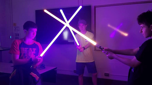 A group of campers build lightsabers at Technology Camp