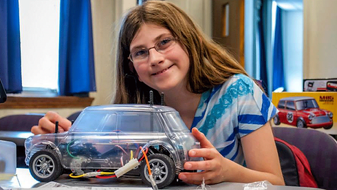 An Emagination Tech Camper holding her radio controlled car
