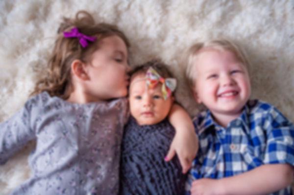 siblings kissing baby sister
