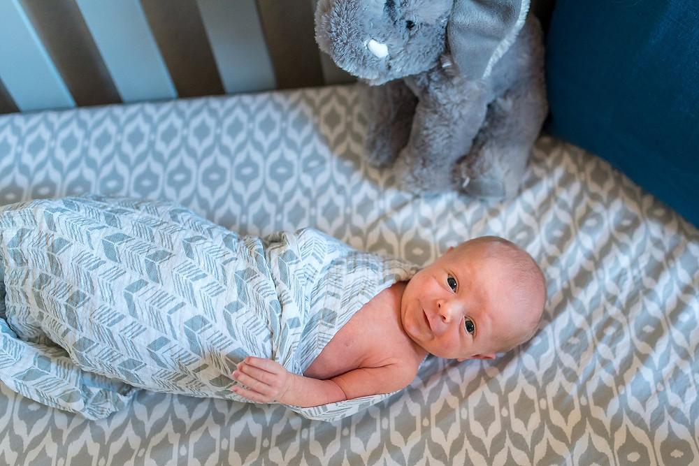 newborn boy smiling in crib