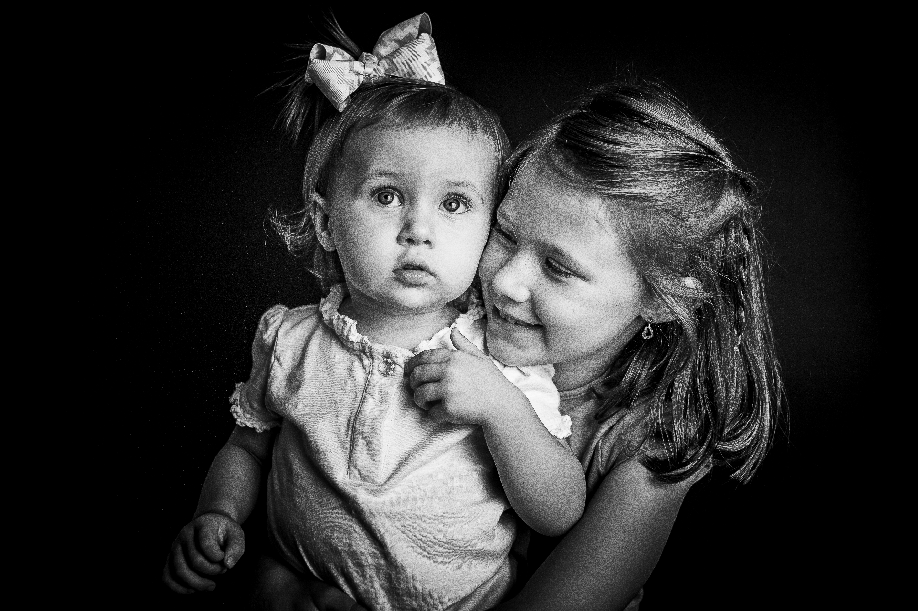 girl hugging younger sister