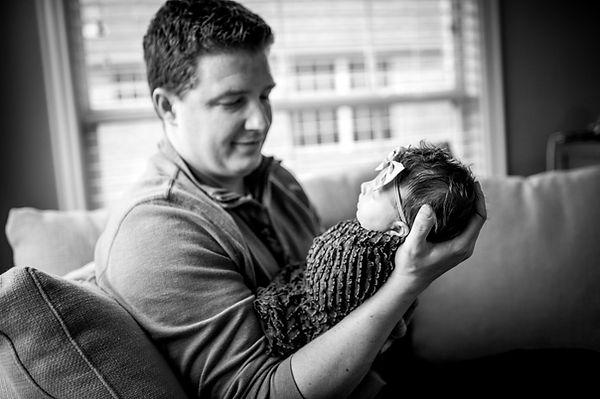 dad admiring newborn daughter