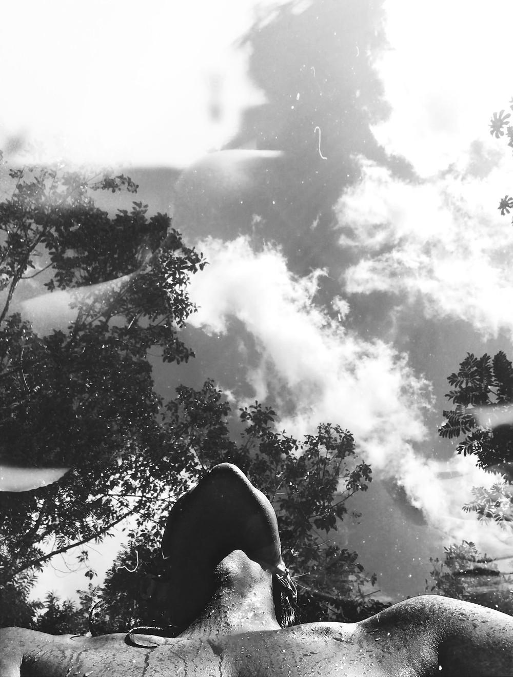 Imagem a contra-plano em preto e branco, onde aparece os ombros, o pescoço e o queixo de uma mulher olhando para cima, atrás dela uma floresta e o céu com nuvens