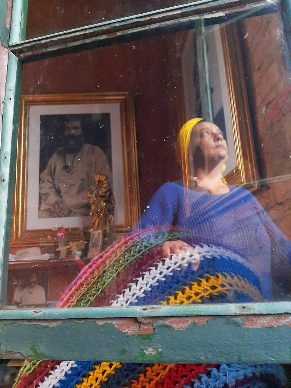 Mulher vestindo casaco azul e turbante amarelo olhando para fora da janela, à frente dela uma manta de crochê colorida, atrás imagem de Hazrat Inayat Khan
