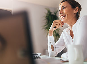 Smiling woman sitting at her desk in off