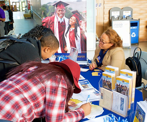 Three college-aged Black students (one with a pony tail, one in a black sweater and black back pack, and one in a red plaid shirt and red floppy hat, learning over a table filling out forms at an information table while a middle-aged Black femme or woman with glasses and light wavy hair watches.