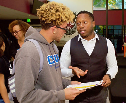 One adult black masc or male or man in a white collared shirt and black vest having a conversation with a young black male or masc or man wearing glasses and a hoodie holding papers.