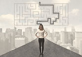 Business woman looking at road with maze and solution concept.jpg