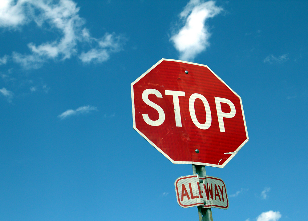 All-way stop sign againt blue sky