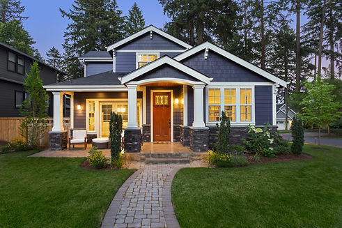 Luxury Home Exterior at Night: Beautiful New House with Green Grass and Landscaping at Twi