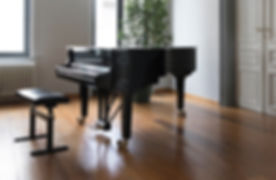 brown grand piano inside white room_edited.jpg