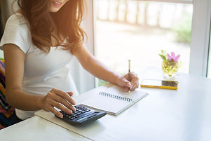 Young woman writes to blank diary and using calculator on a white table at home..jpg