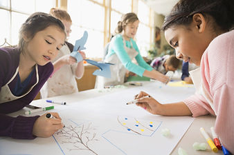 Kids drawing together on a large sheet of paper
