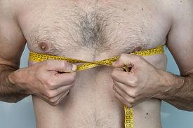 caucasian thin man with chest hair measu
