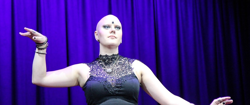 A woman with no hair dancing and looking off into the distance.