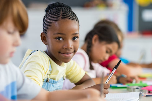 Smiling african girl sitting at desk in