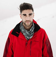 Benj Brooking wearing a red snow jacket and a black and white scarf