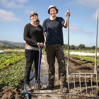 Fiona Heargraves and Bailey Peryman standing together in a farm holding two pitchforks and wearing gumboots
